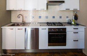 Cucina con mattonelle color crema e disegni azzurri